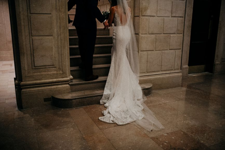 866x578px.bride_and_groom_holding_hands_walking_up_stone_staircase.jpg