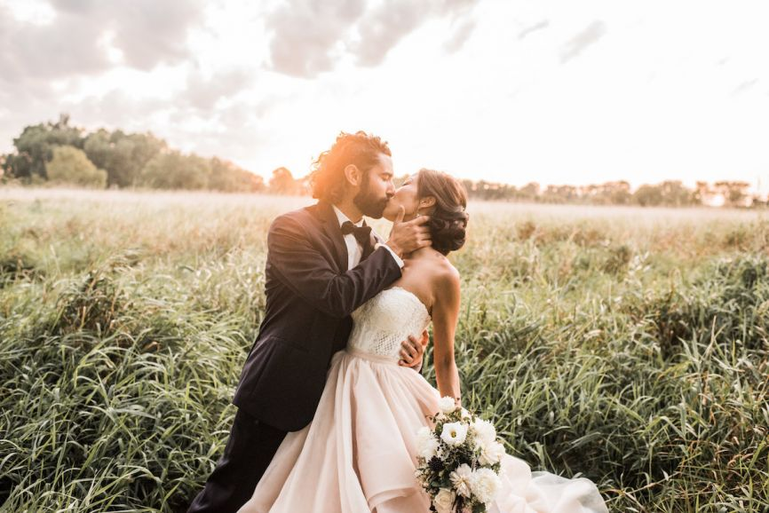866x578px.groom_holding_kissing_bride_in_field_at_sunset.jpg