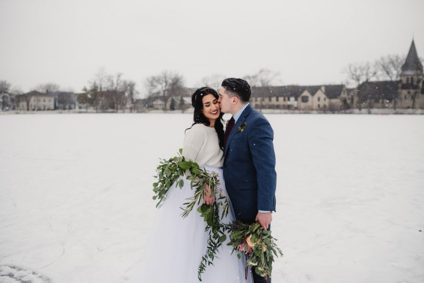 866x578px.groom_kissing_brides_cheeck_at_snowy_park.jpg
