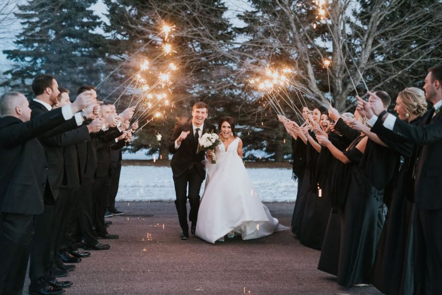 866x578px.wedding_couple_smiling_running_under_sparkler_exit.jpg