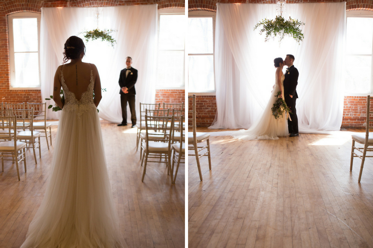 aisle_view_of_bride_and_groom_ceremony_kiss_wood_floors_bright_windows.jpg