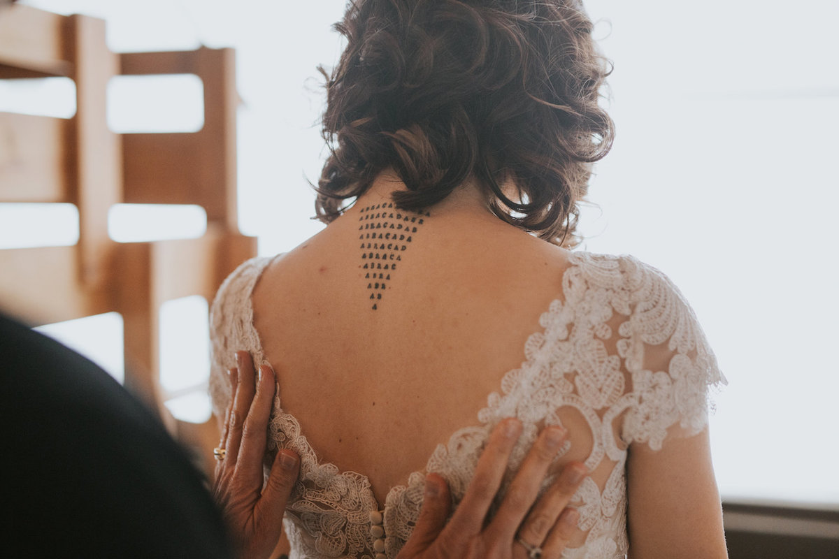 back_of_bride_in_lace_gown_black_triangle_tattoo.jpg
