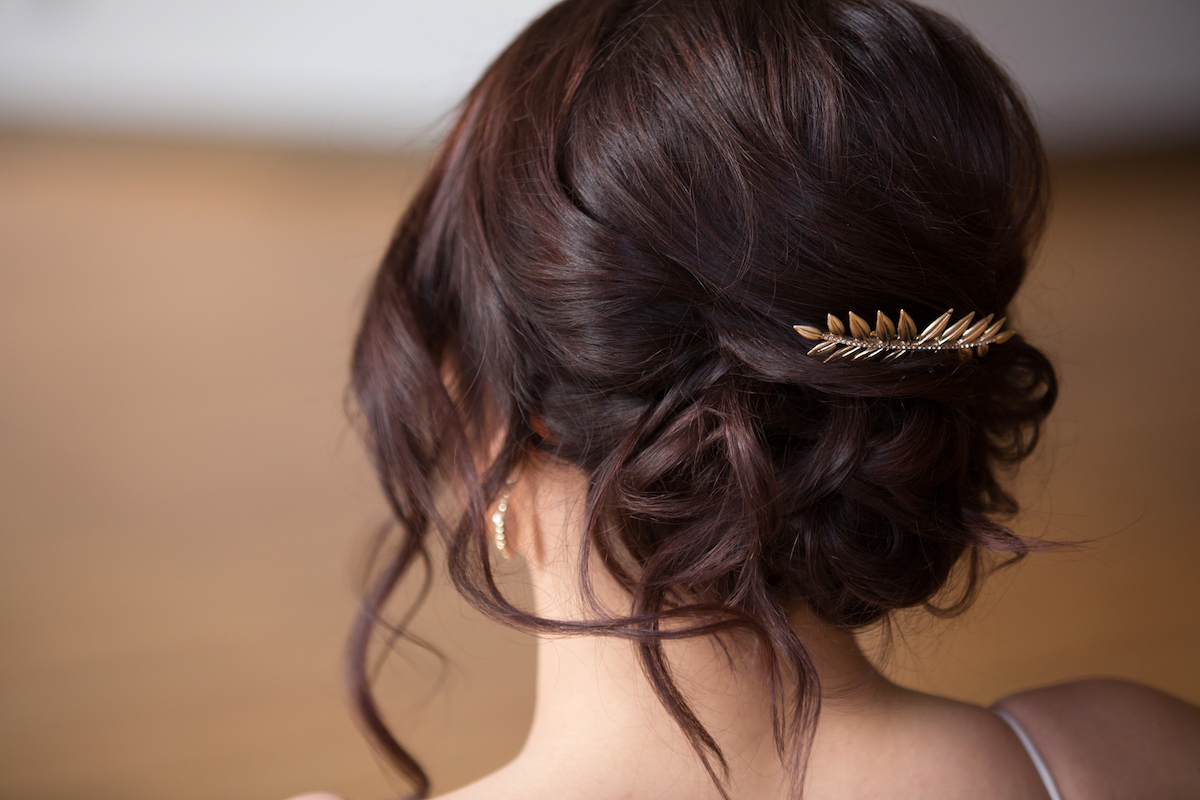 back_view_of_bridal_messy_bun_with_gold_leave_accent_piece.jpg