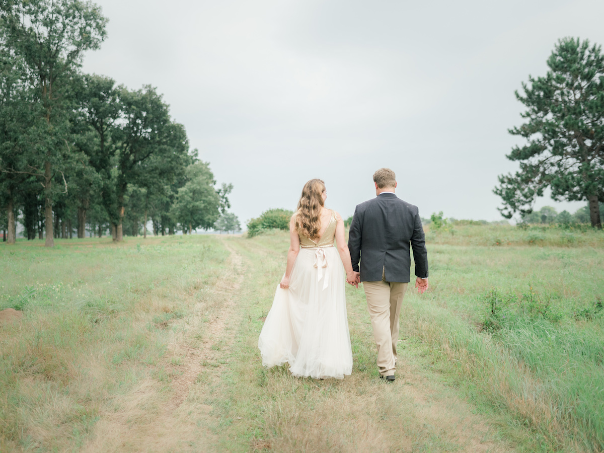 back_view_of_bride_with_bow_walking_hand_in_hand_with_groom.jpg