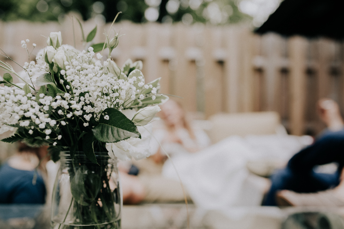 backyard_wedding_green_leaves_white_flowers_glass_vase.jpg