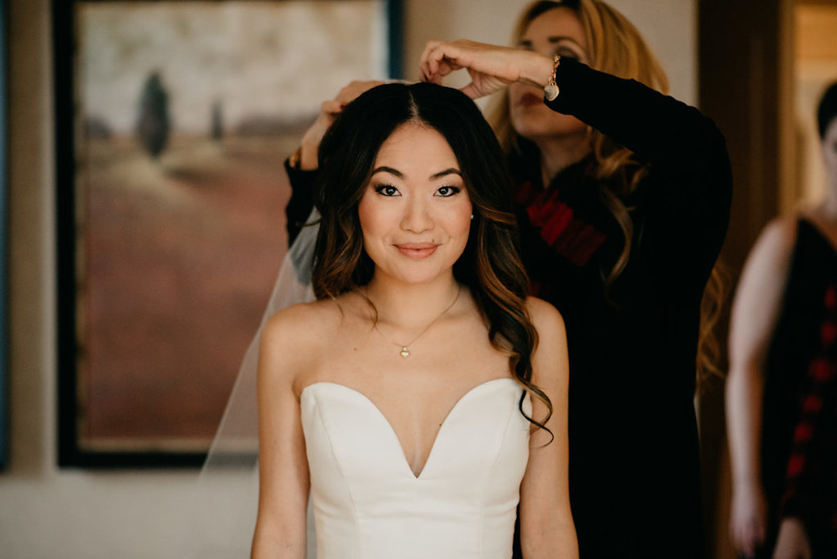 beautiful_bride_getting_ready_viel_placed_in_hair_smiling.jpg