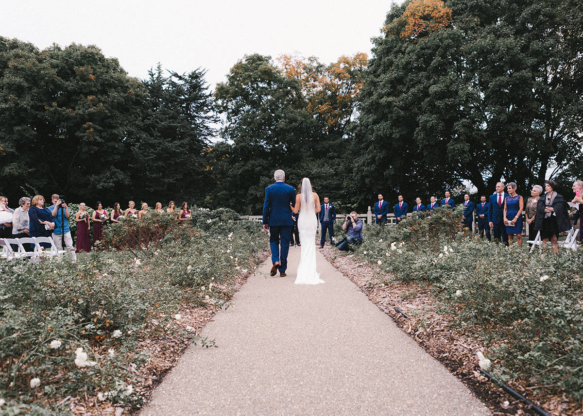 behind_shot_father_walking_daughter_down_garden_aisle.jpg