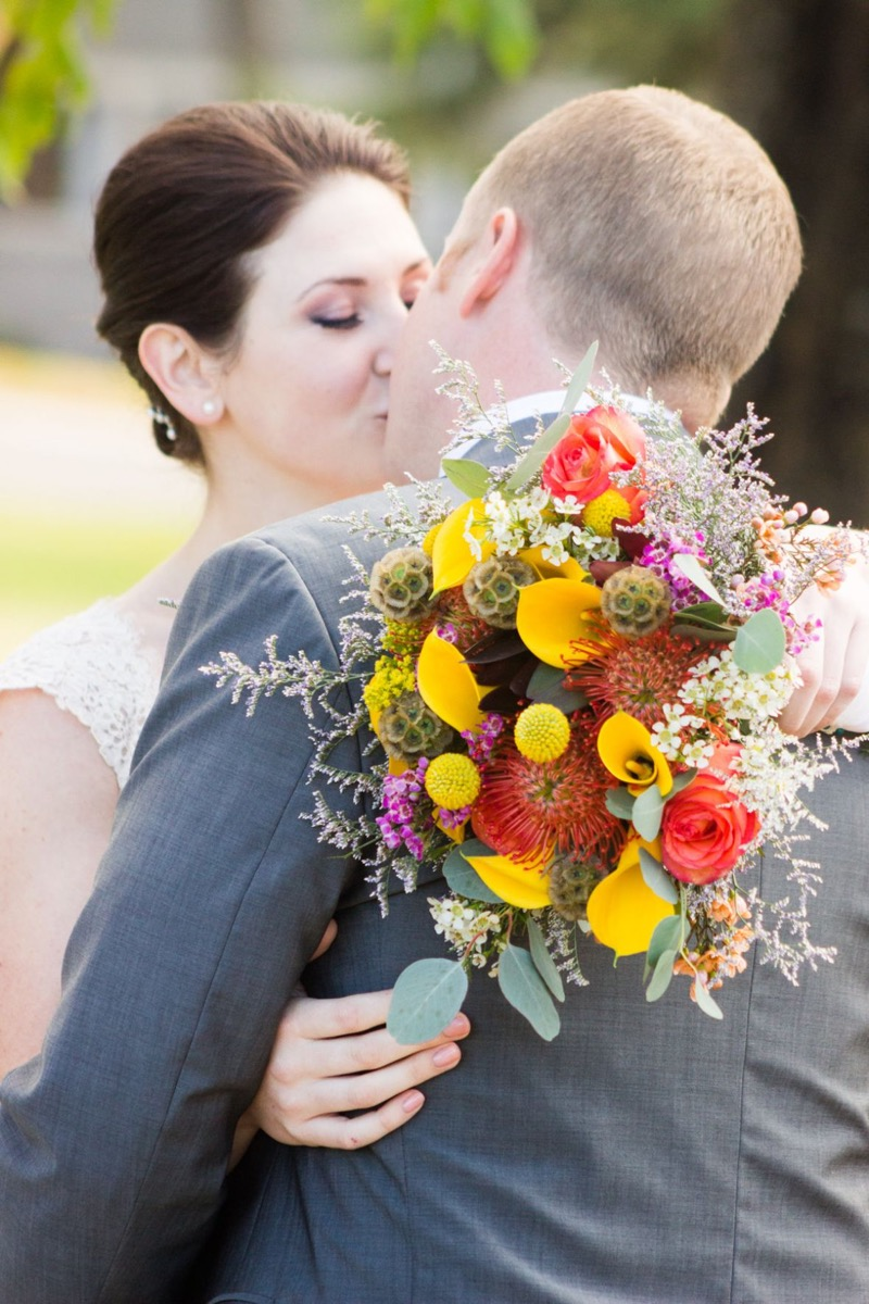 behind_shot_of_yellow_bouquet_newlyweds_kissing.jpg
