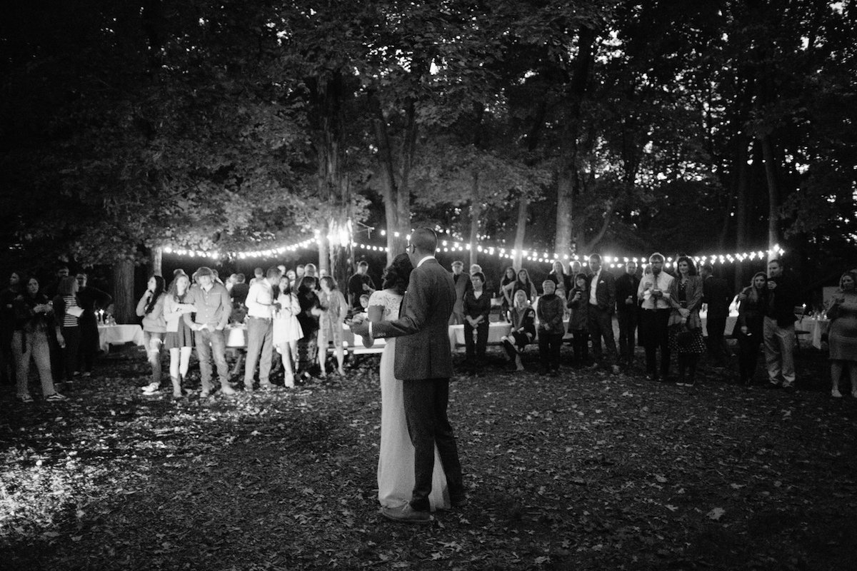 black-and_white_photo_of_vintage_bride_and_groom_first_dance_in_woods_camp_wedding.jpg