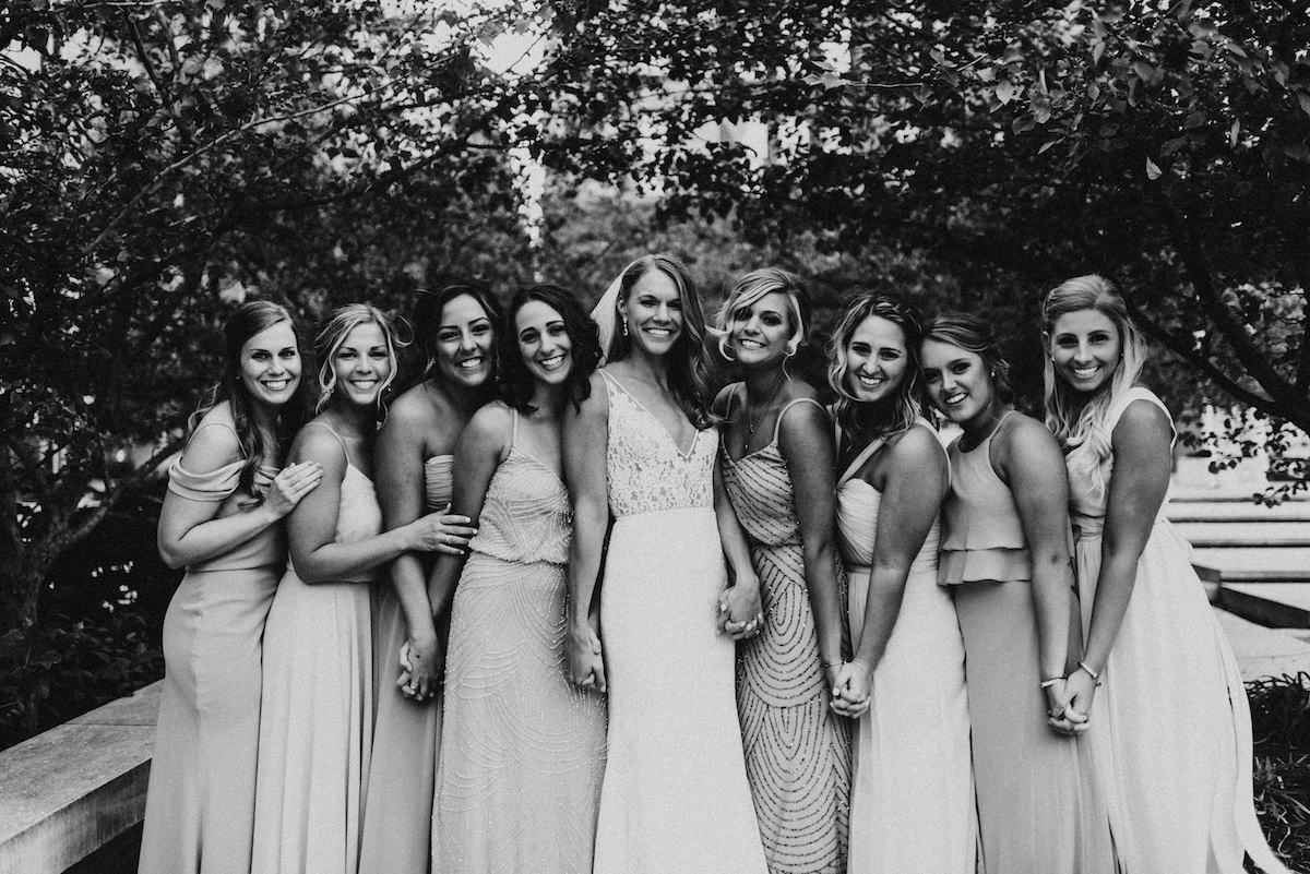 black_and_white_bridal_party_holding_hands_by_trees_in_city.jpg