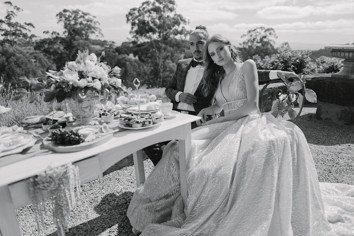 black_and_white_bride_and_groom_sitting_together_french_lunch.jpg
