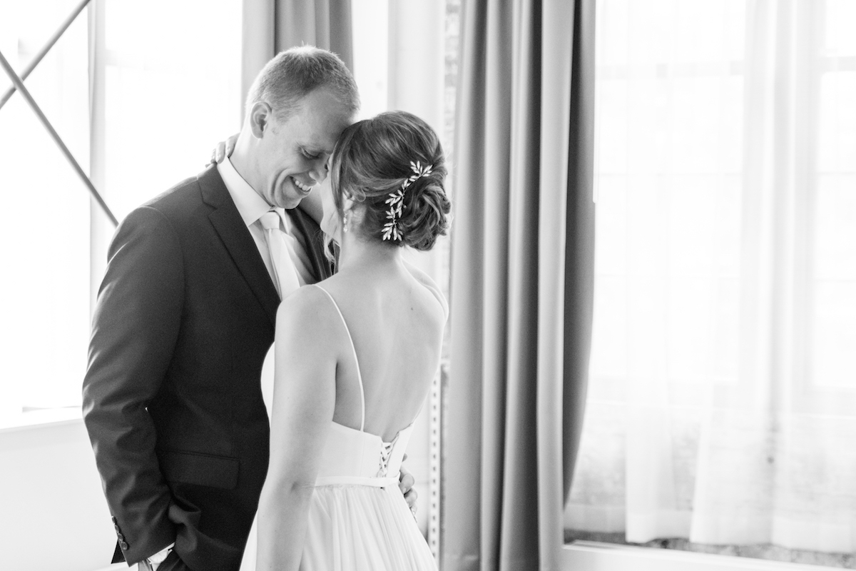 black_and_white_bride_arm_around_grooms_shoulder_foreheads_touching_groom_smiling_bright_backround.jpg