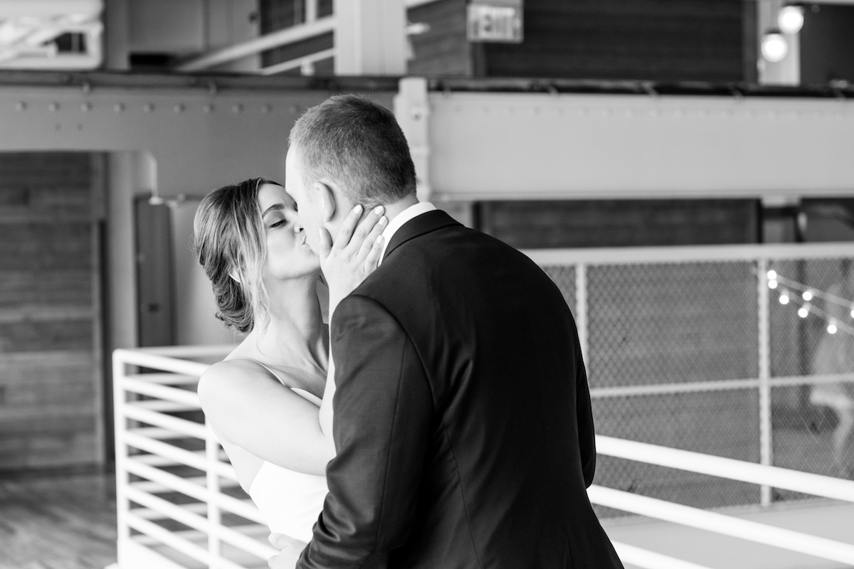 black_and_white_bride_holding_grooms_face_kissing_him_indoor_industrial_venue.jpg