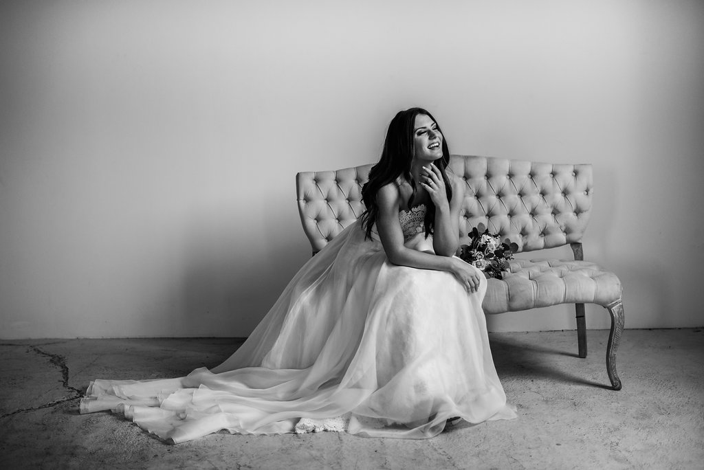 black_and_white_bride_sitting_on_chair_smiling.JPG