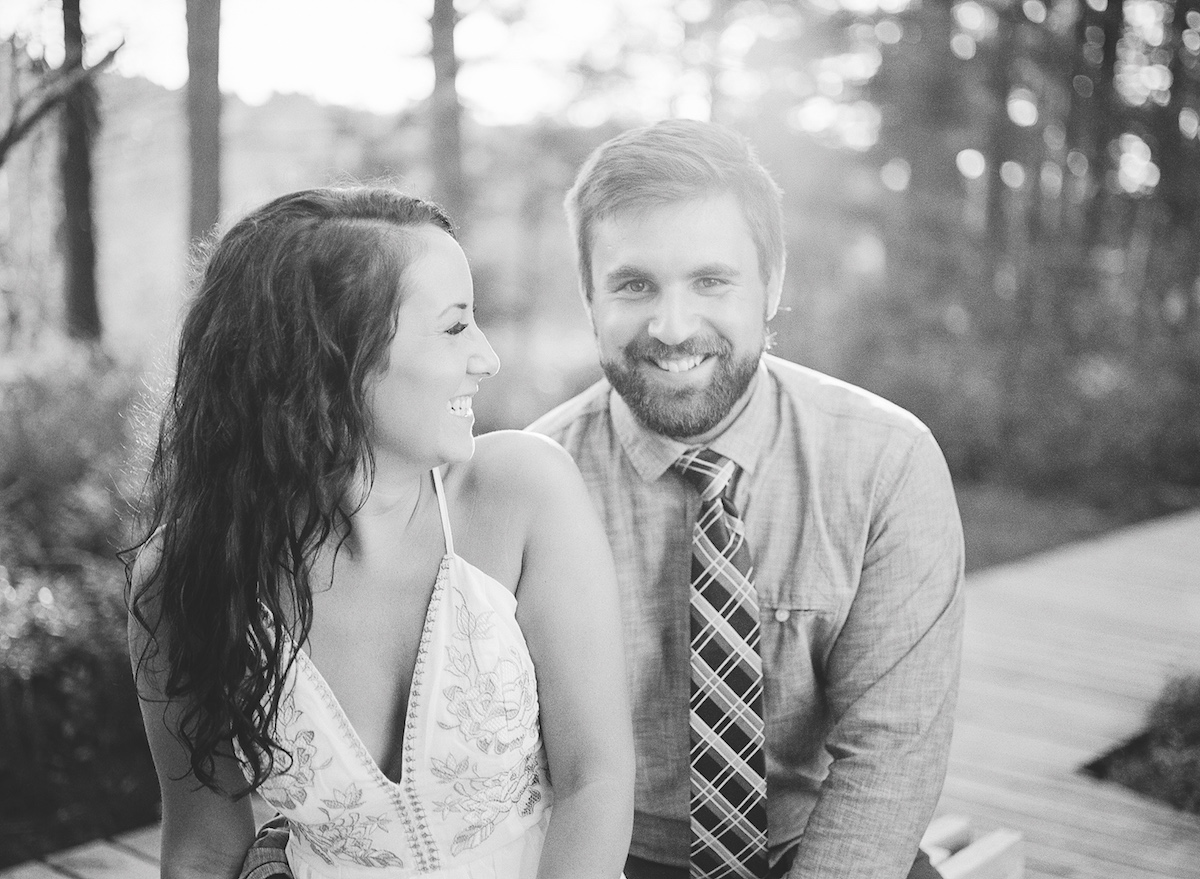 black_and_white_engagement_photo_couple_smiling_laughing_in_sunny_forest.jpg