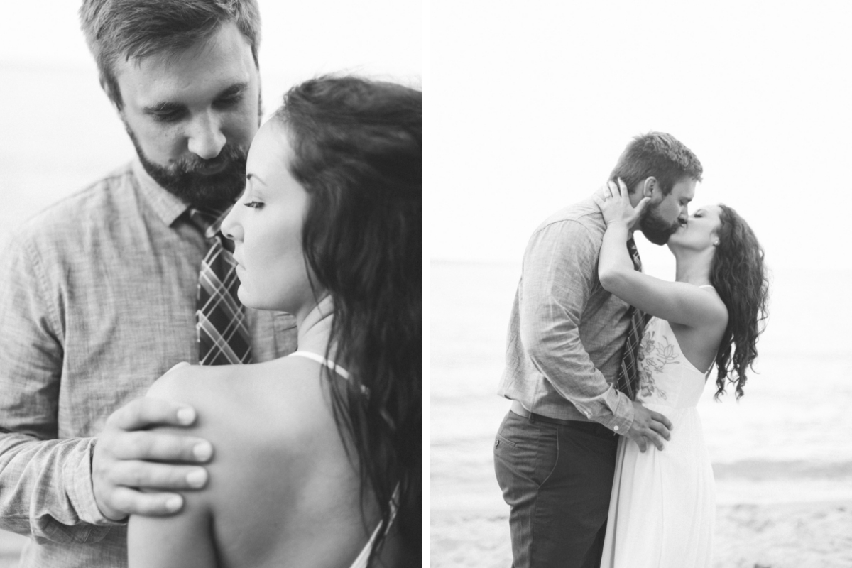 black_and_white_engagement_photos_kissing_passionately_in_front_of_water_on_beach.jpg