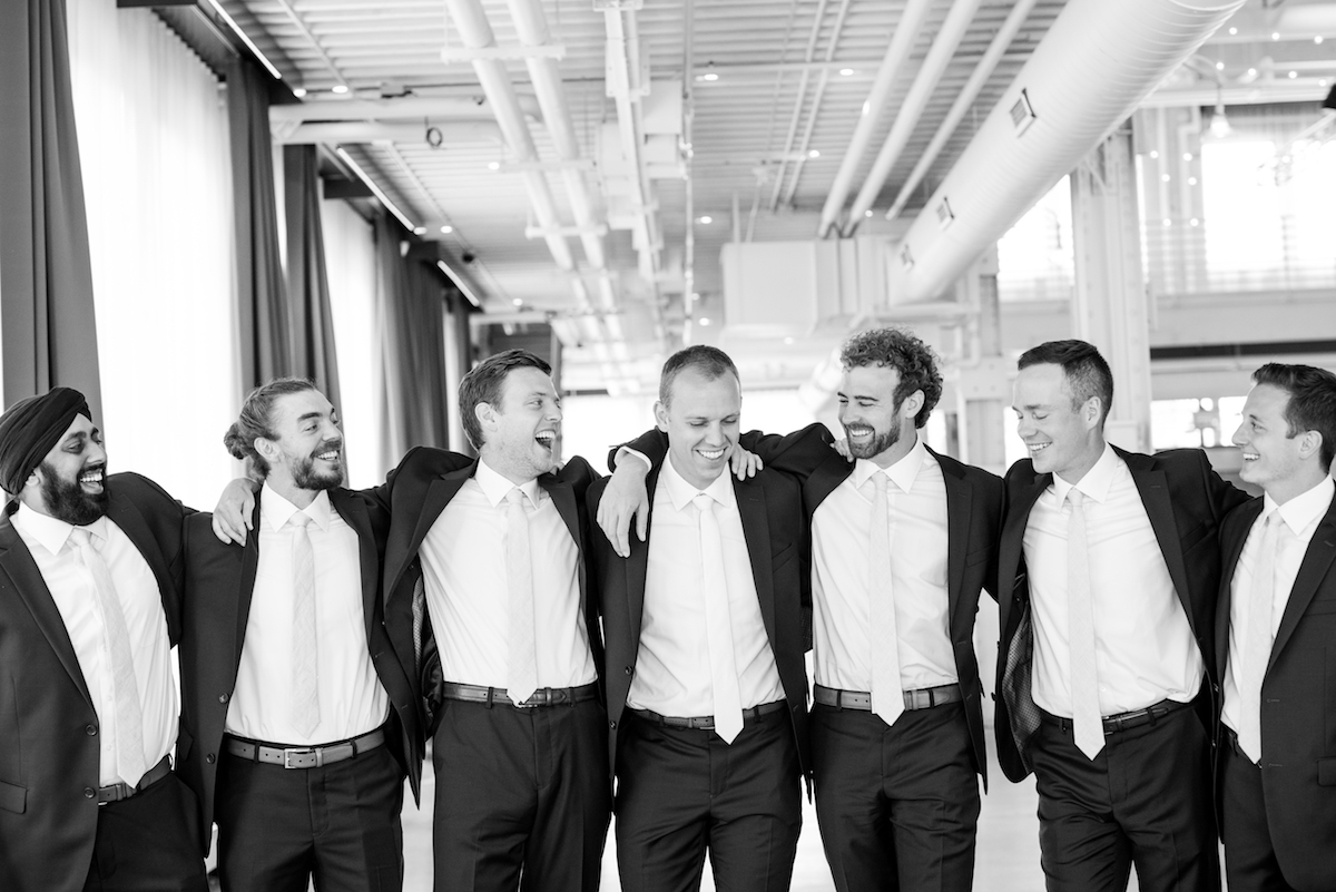 black_and_white_groom_and_groomsmen_arms_around_each_other_laughing_industrial_wedding_venue.jpg