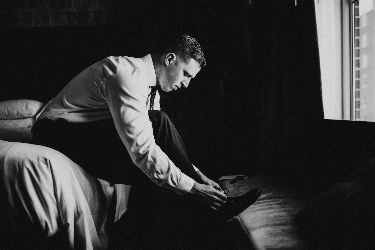 black_and_white_groom_getting_ready_putting_on_shoes.jpg