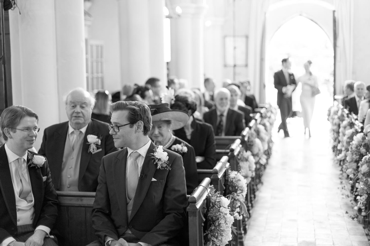 black_and_white_groom_sitting_in_church_pew_before_ceremony.jpg