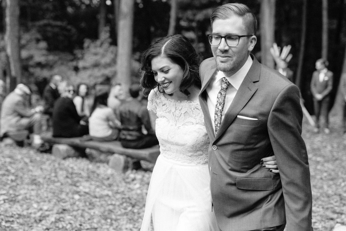 black_and_white_photo_bride_and_groom_smiling_walking_down_aisle_after_ceremony.jpg