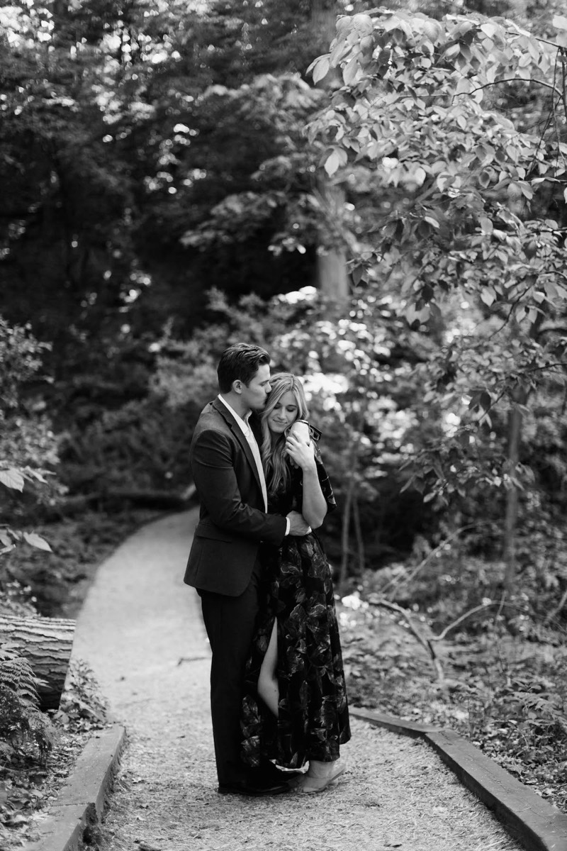 black_and_white_photo_couple_standing_in_woods_forehead_kisses.jpg