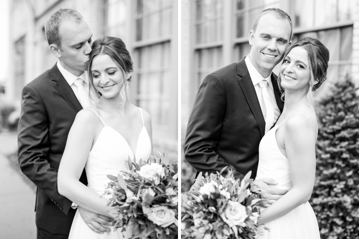 black_and_white_photo_groom_standing_behind_bride_kissing_her_head_bride_holding_bouquet_standing_outside.jpg