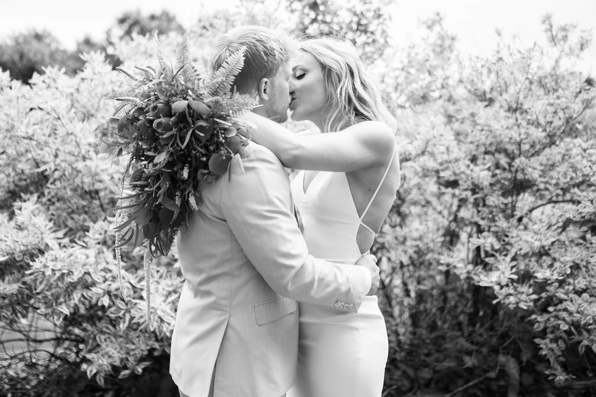 black_and_white_photo_of_bride_and_groom_kissing_outdoors.jpg