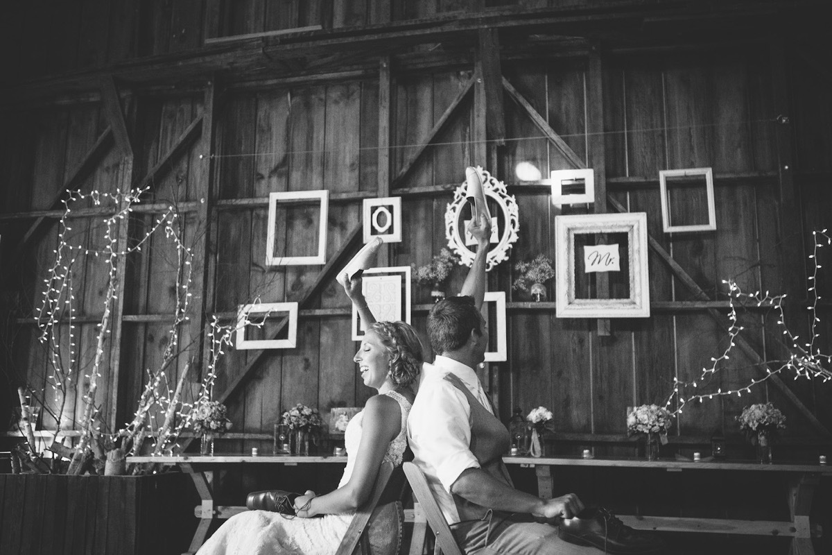 black_and_white_photo_of_couple_playing_shoe_game_wedding.jpg