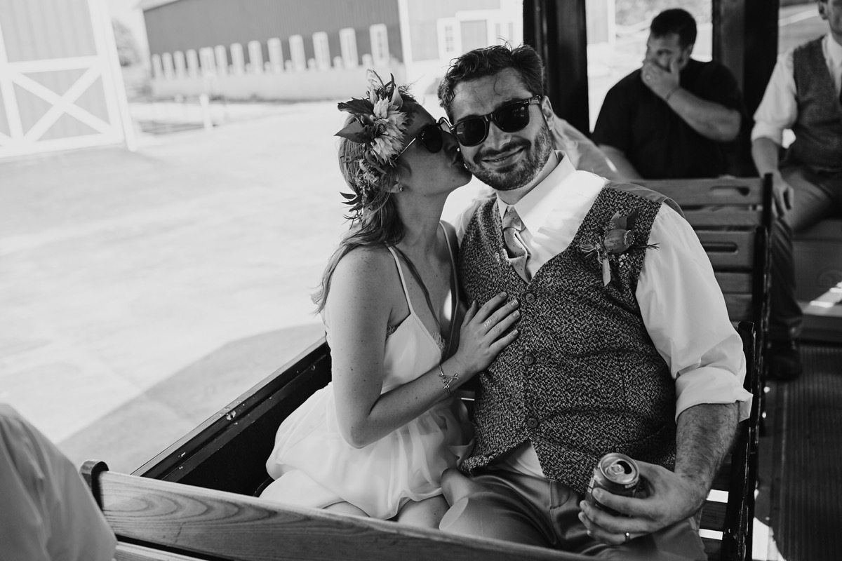 black_and_white_photo_wedding_couple_kissing_on_trolly.JPG