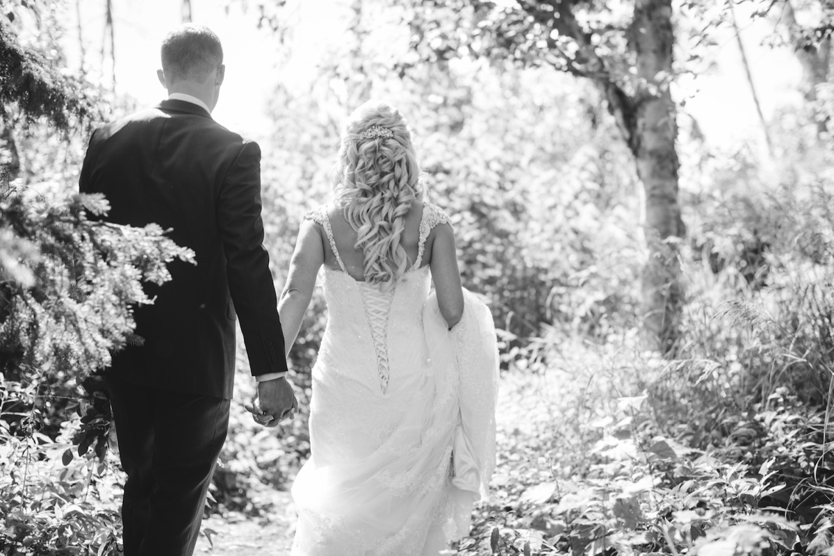 black_and_white_picture_of_newlyweds_holding_hands_by_trees.jpg