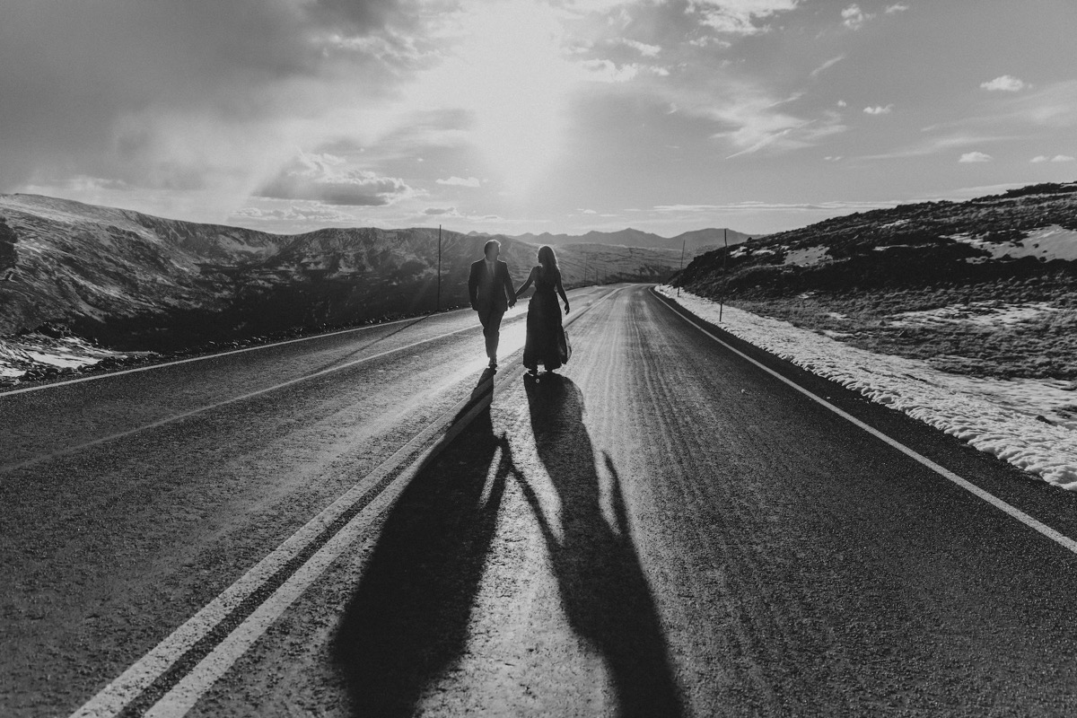 black_and_white_portrait_couple_walking_in_middle_of_street.jpg