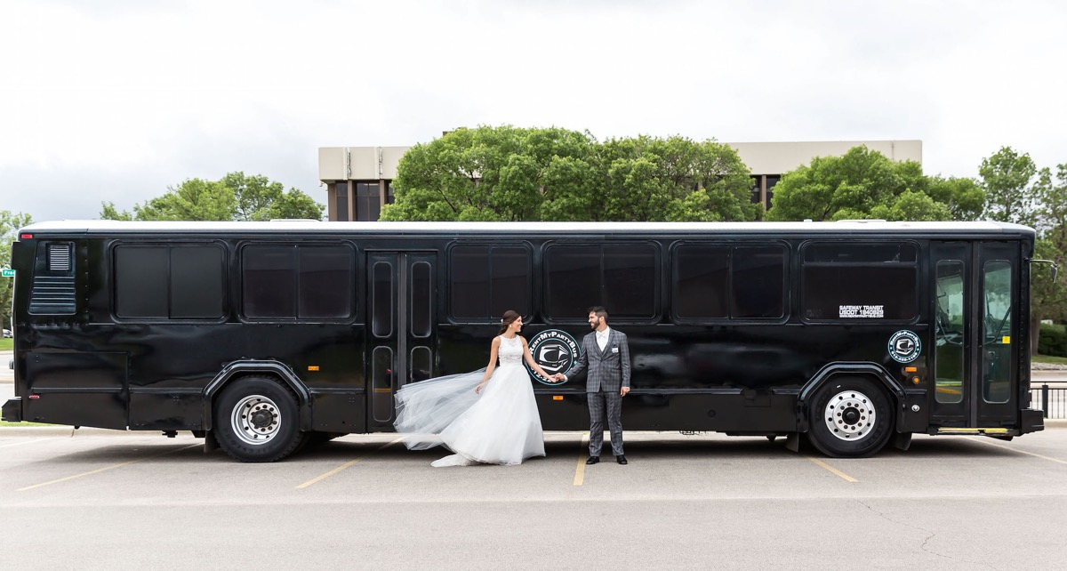 black_party_bus_minnesota_bride_groom_holding_hands_in_front.jpg