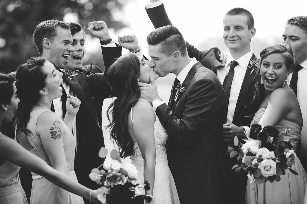 black_white_bridal_party_cheers_for_kiss.jpg