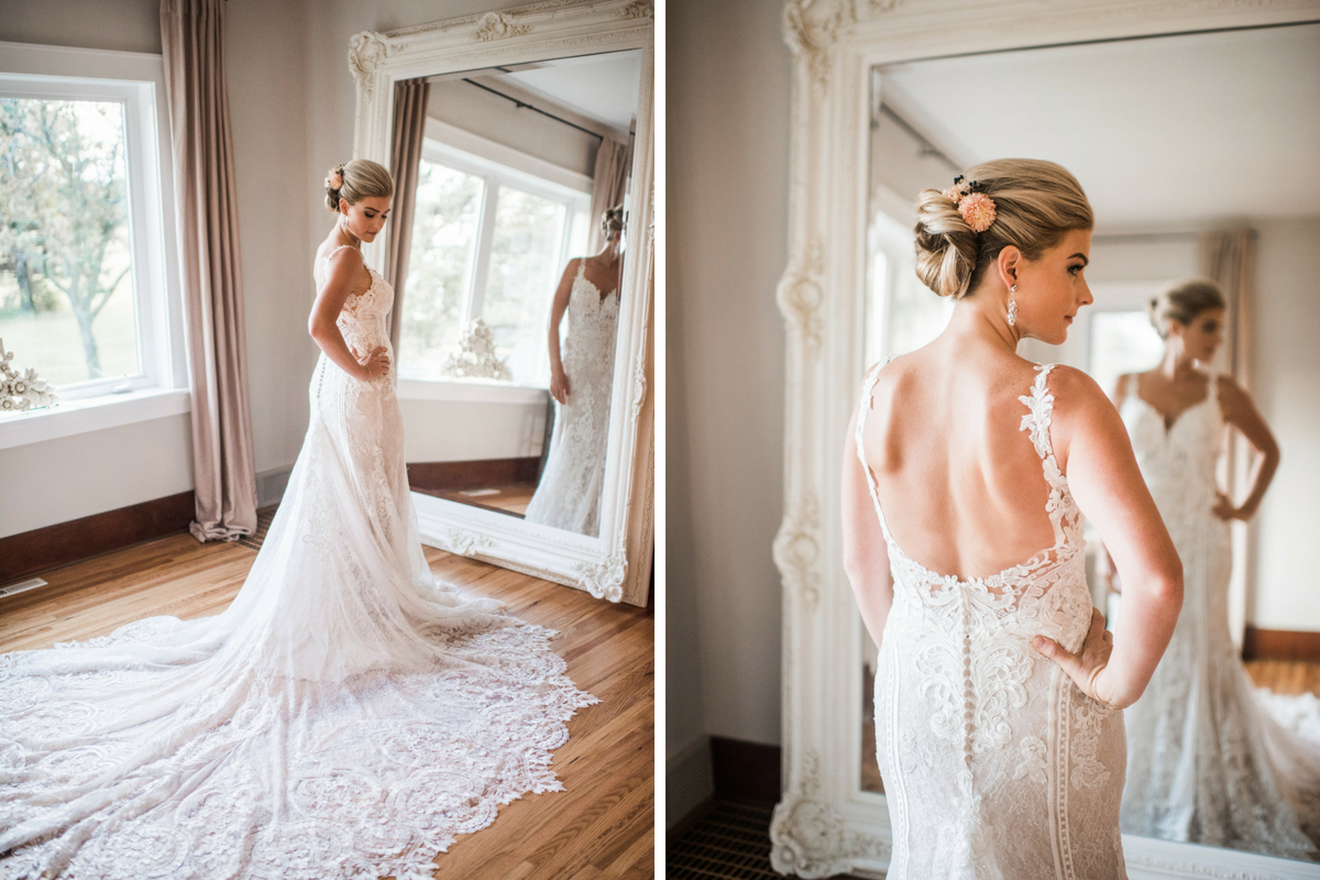 blonde_bride_in_lace_gown_long_train_looking_in_mirror_bright_room.jpg