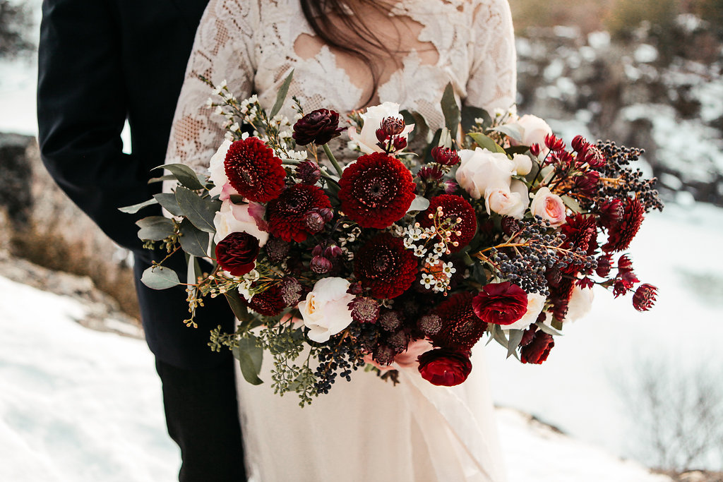 body_shot_of_bride_groom_holding_giant_red_bouquet.jpg