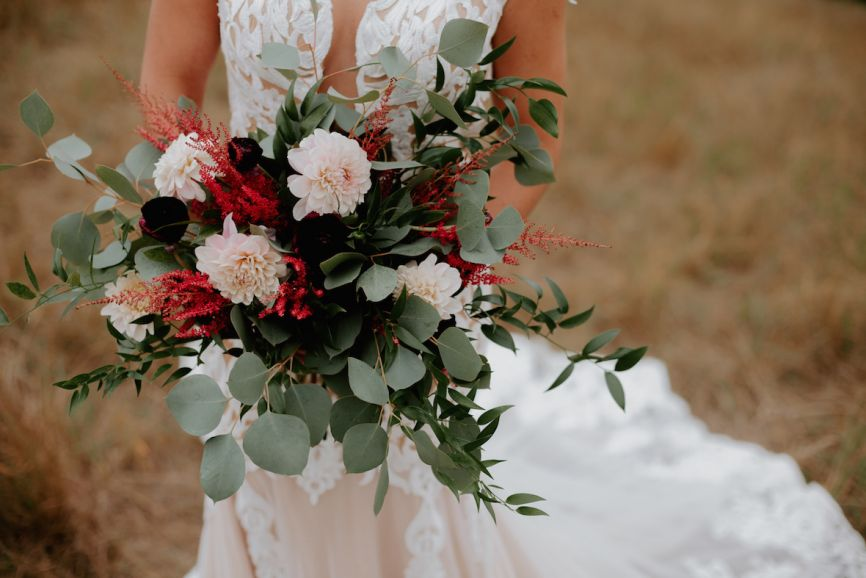 body_shot_of_bride_holding_red_fall_bouquet.jpg