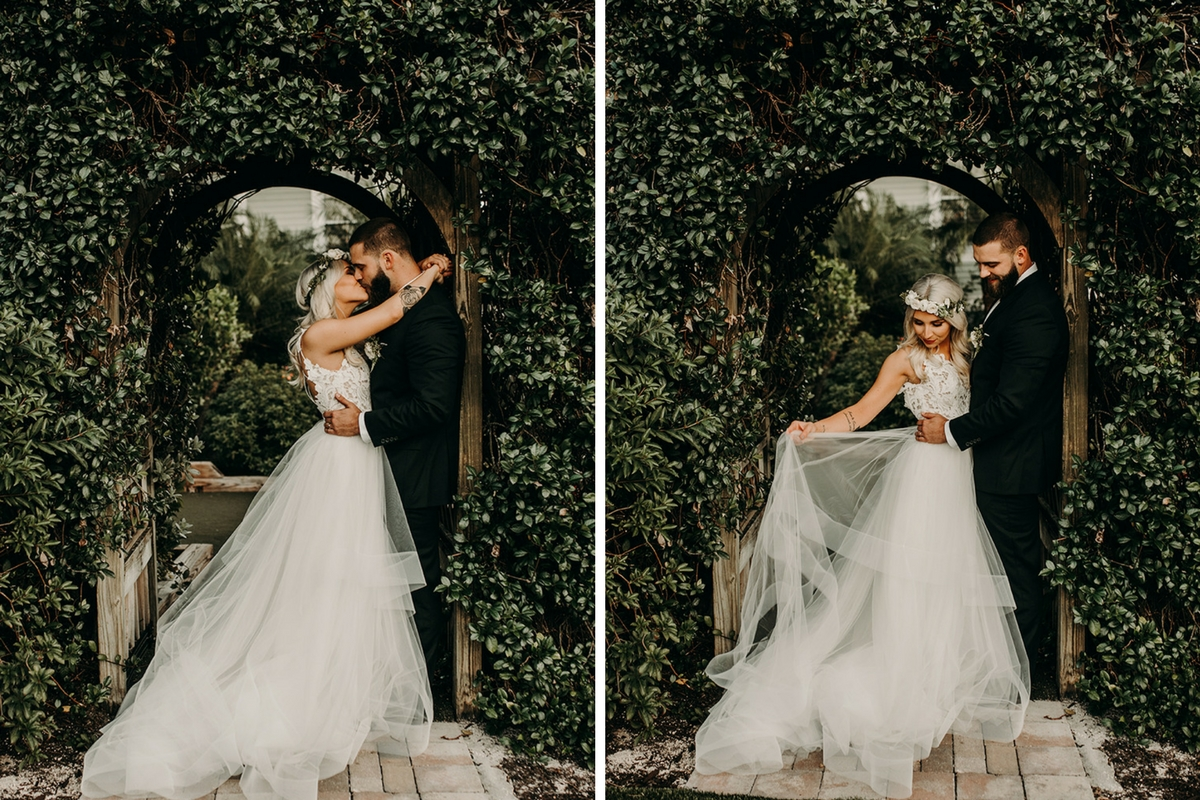 bohemian_bride_and_groom_kissing_under_garden_arch.jpg