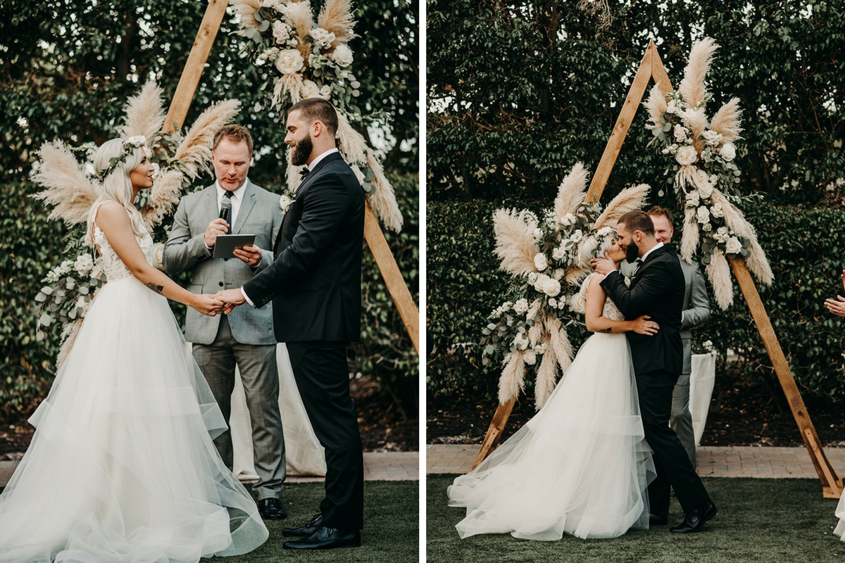 boho_bride_and_groom_first_kiss_under_wedding_arch.jpg