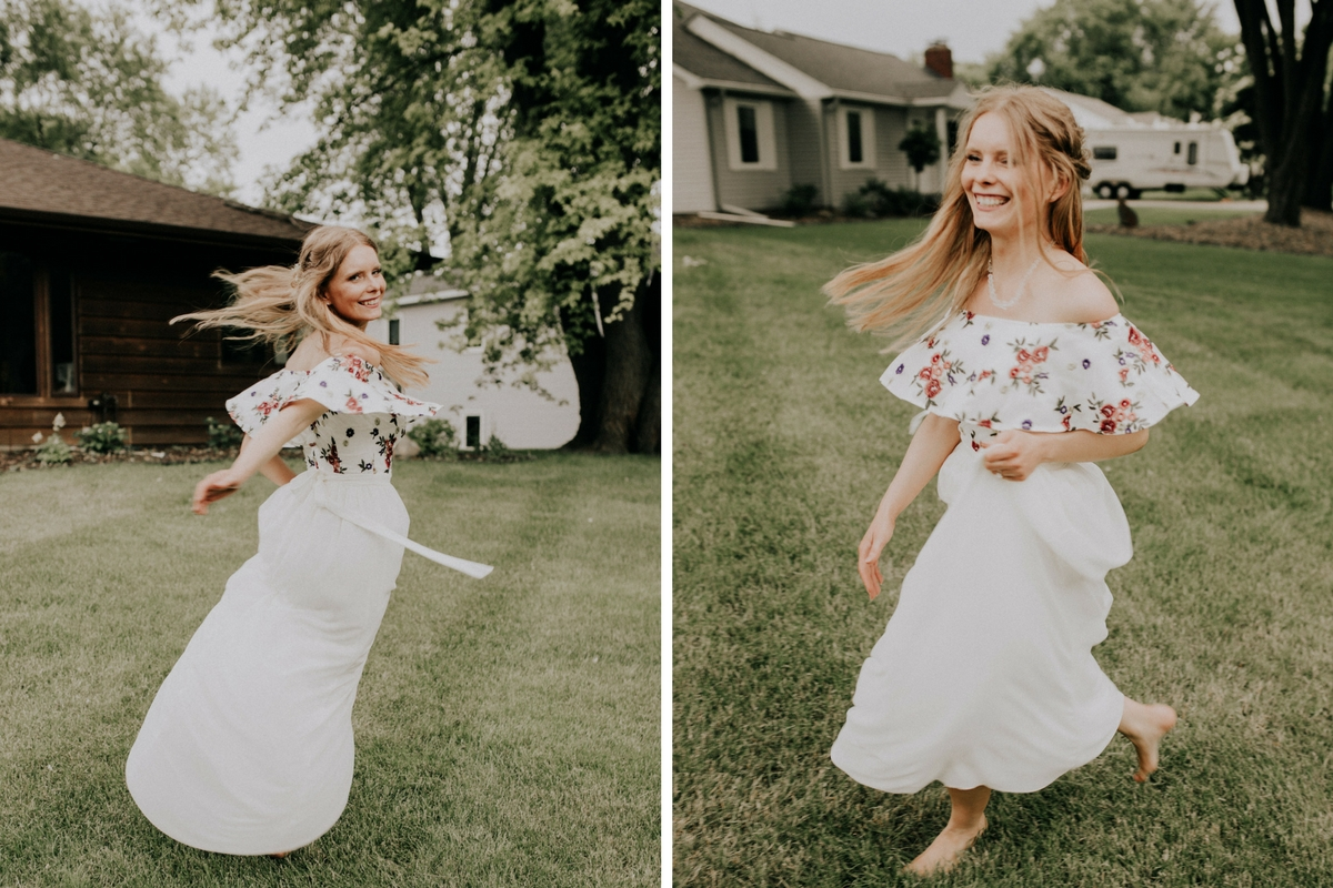 boho_bride_in_floral_dress_white_skirt_twirling_in_grass.jpg