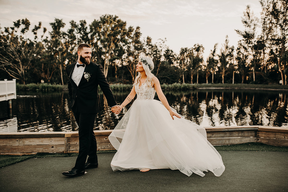 boho_bride_in_white_lace_gown_walking_with_groom_florida.jpg