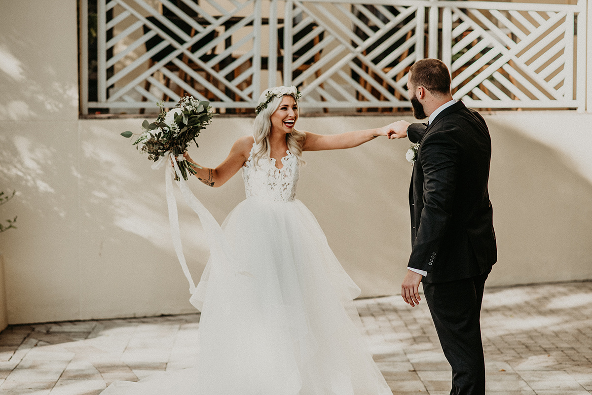 boho_bride_laughing_during_first_look_with_groom.jpg