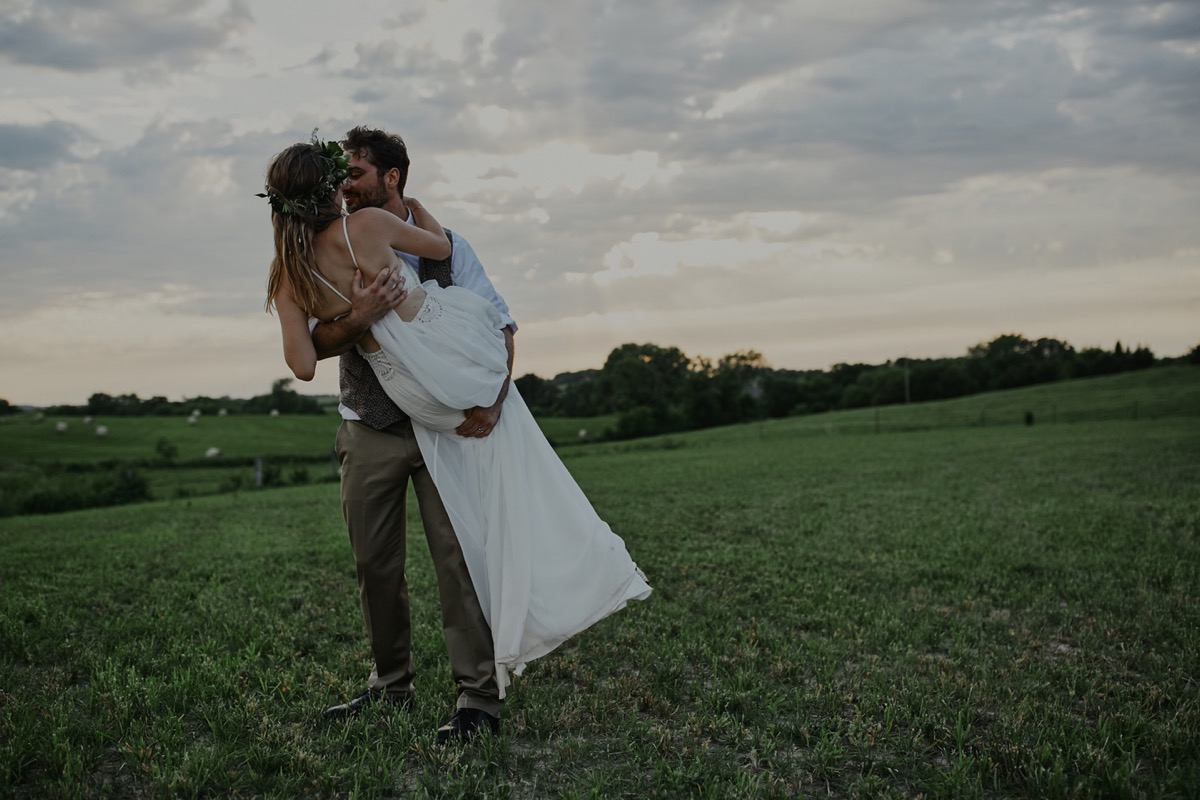 boho_farm_wedding_groom_holding_bride_in_field.JPG