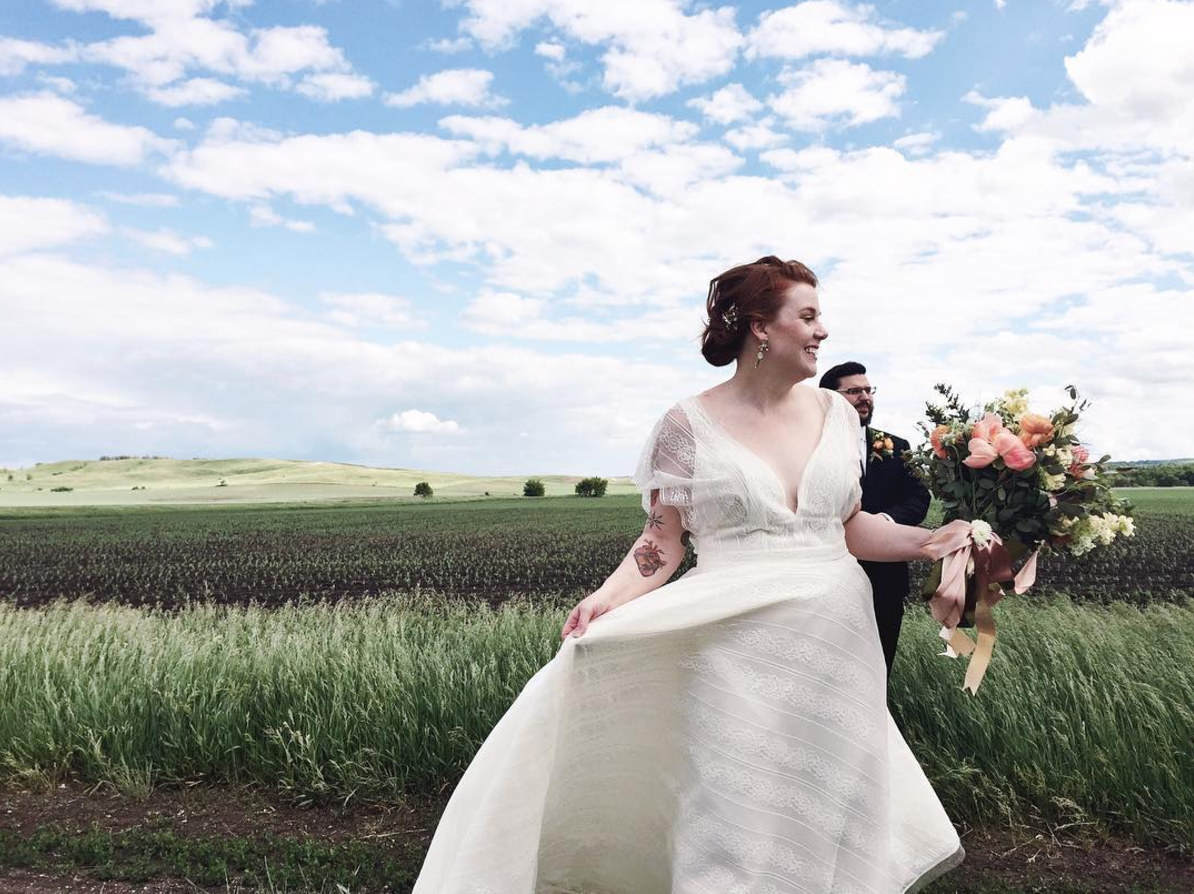 boho_simple_bridal_gown_standing_in_empty_green_dirt_field_minnesota_wedding_videography_taupe_bouquet_ribbons.png