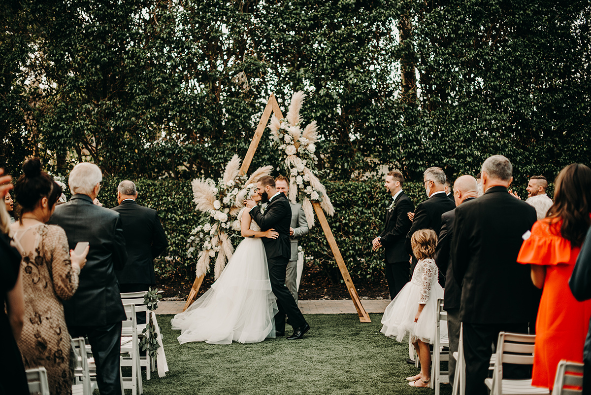 boho_wedding_bride_and_groom_kissing_under_wooden_arch.jpg