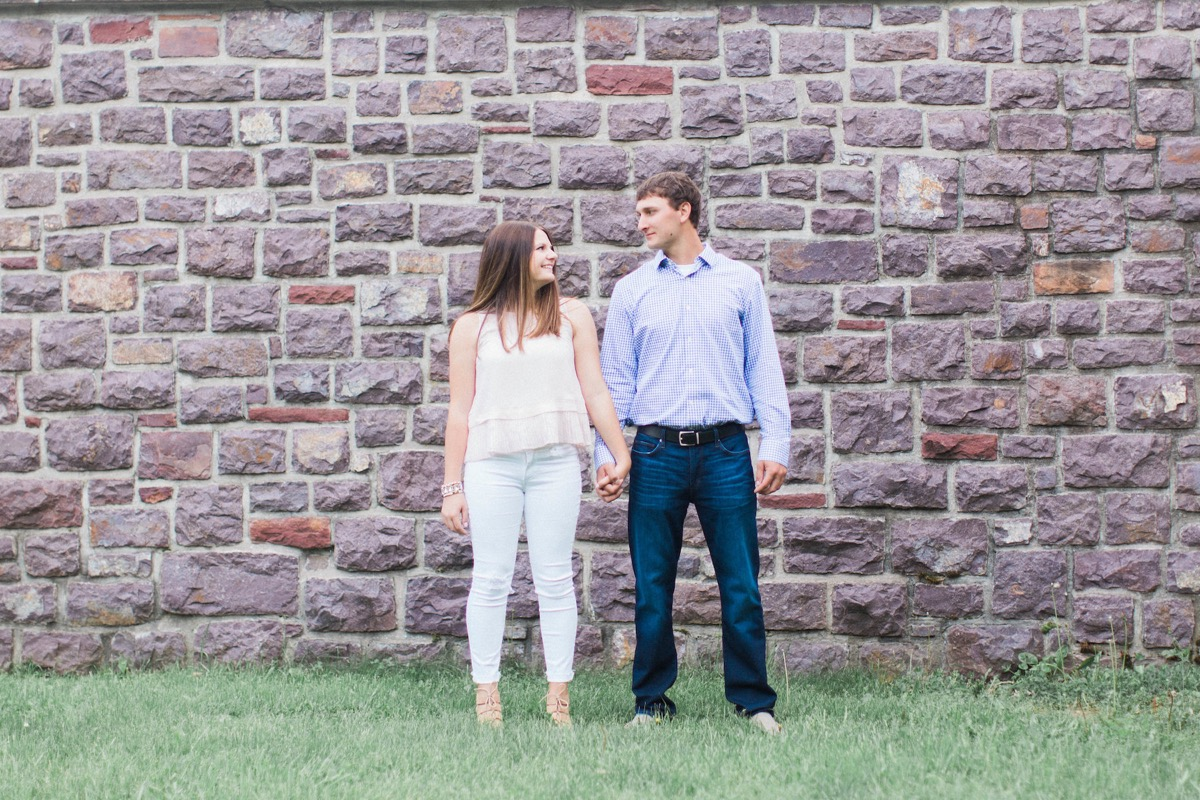 brick_wall_looking_at_each_other_engagement_photos.jpg