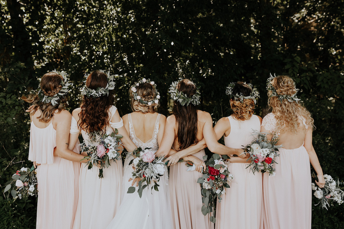 bridal_party_facing_backwards_pink_white_gowns_flower_crowns_floral_bouquets.jpg