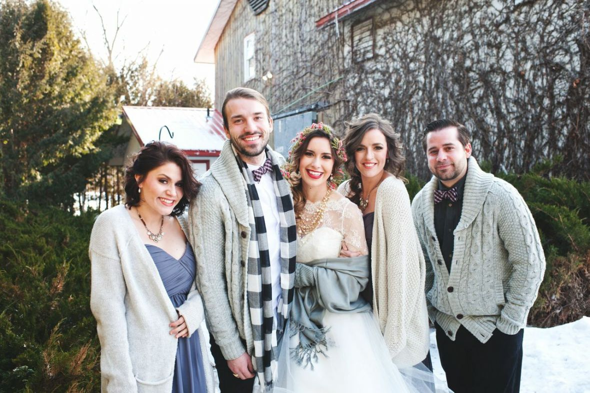 bridal_party_huddled_together_in_the_snow_in_gray_shawls.jpg