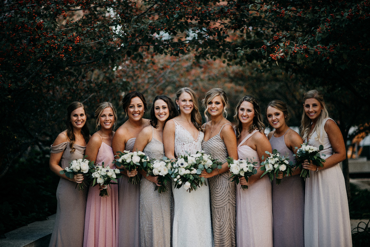 bridal_party_mismatched_bridesmaid_dresses_smiling_by_trees.jpg