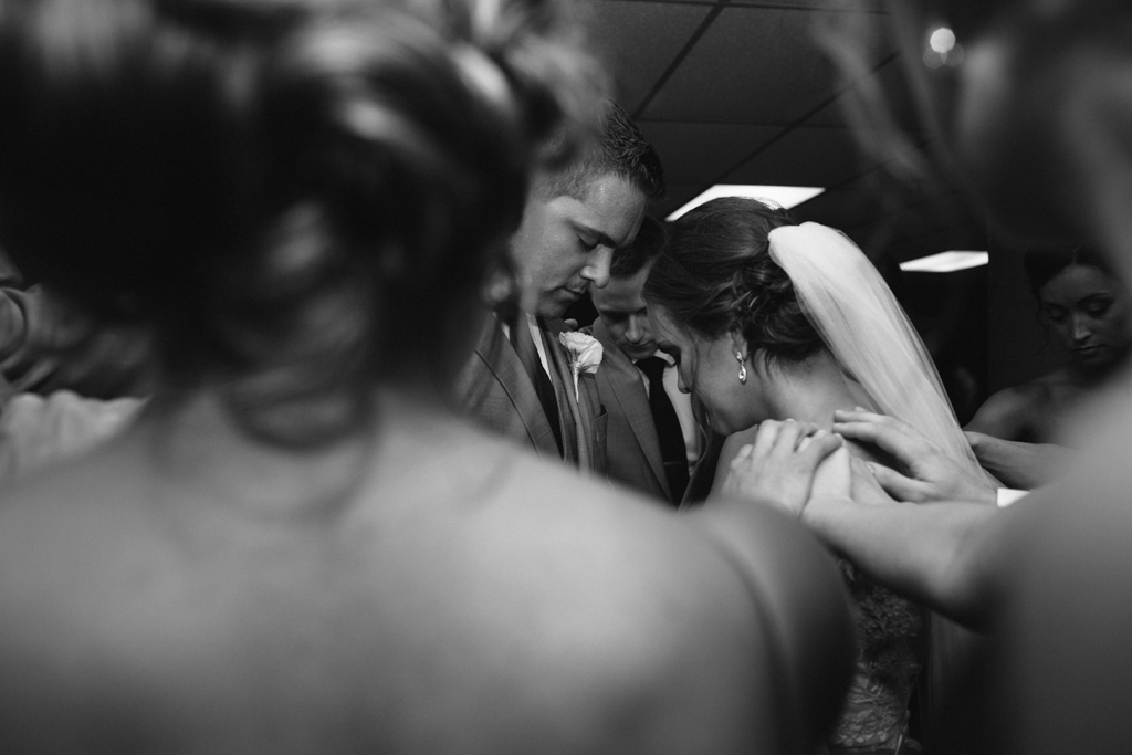 bridal_party_placing_hands_on_couple_praying.jpg