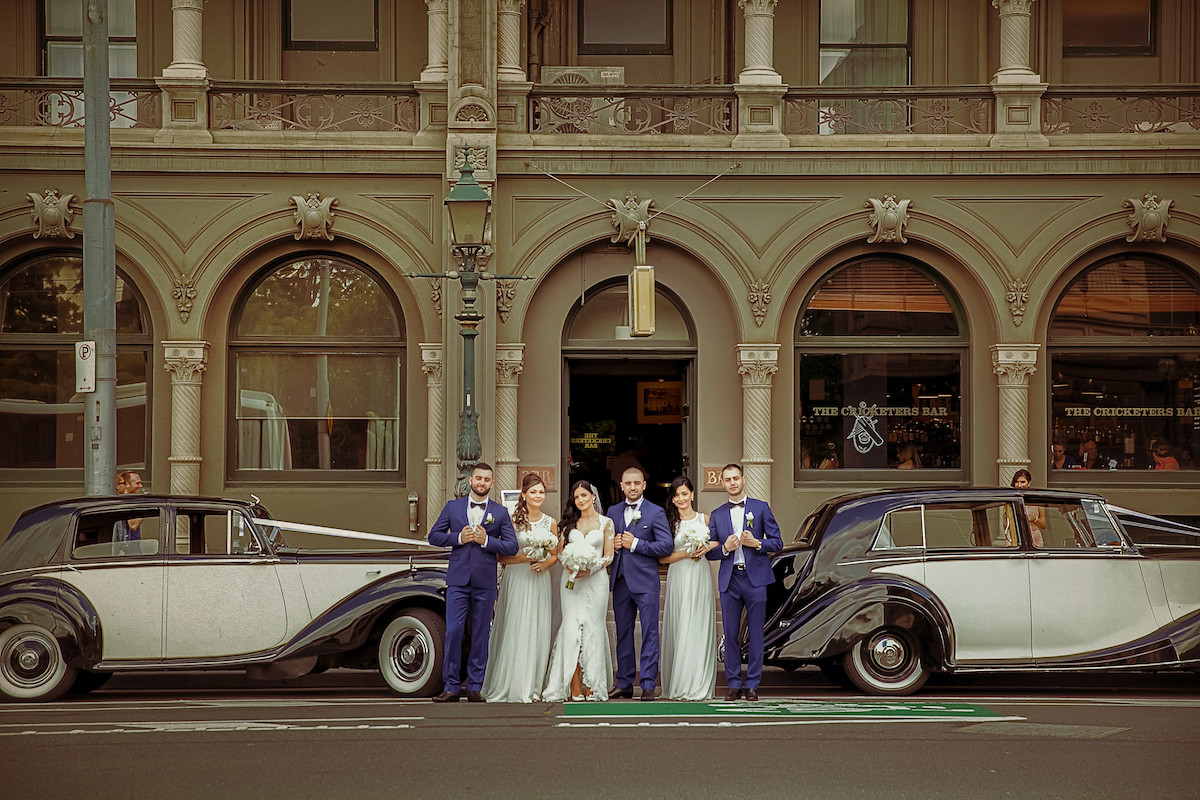 bridal_party_standing_in_front_of_large_stone_building_between_two_old_fashioned_cars_view_from_across_street.jpg
